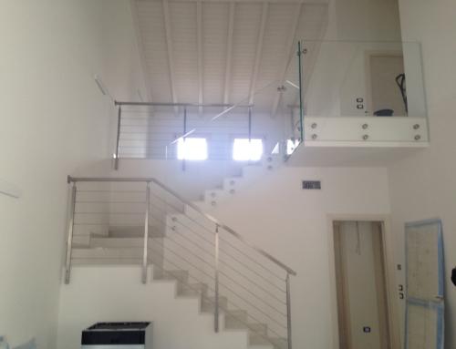 Parapetto con piantoni e cordini in acciaio inox e vetri con fissaggio laterale